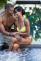 Couple in swimsuits cuddling by pool