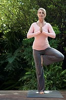 Middle_aged woman in yoga pose outdoors