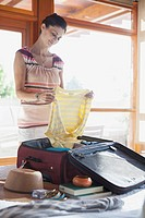 Mid_adult woman unpacking suitcase