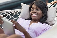 Middle_aged woman with pc tablet in hammock