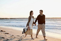 Couple enjoying a walk along the beach