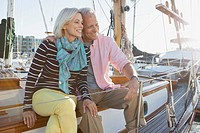 Senior couple sitting on sailboat.