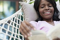 Beautiful African American woman with book in hammock