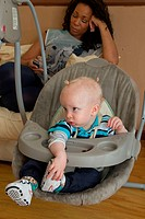 Small boy in rocker with mother in background This photo has extra clearance covering Homelessness, Mental Health Issues, Bullying, Education and Excl...