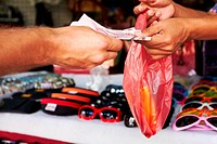 Closeup of money exchanging hands at a market after buying a pair of sunglasses