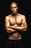 Portrait of a handsome young shirtless man on a black background