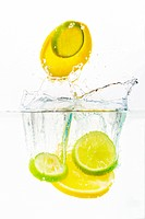 Studio shot of lemon and lime slices being dropped into clear water