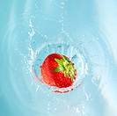 High angle studio shot of a single strawberry being dropped into blue water with copyspace