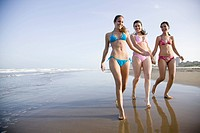 Young Women Walking Along Beach