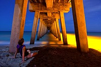 woman sitting under pier at night, time exposure. Photo taken at the pier at Venice Beach, Florida, USA