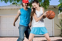Two Teenagers Playing Basketball in Driveway