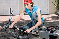 Teenager Fixing Bicycle