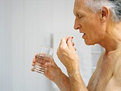 An elderly man takes medication