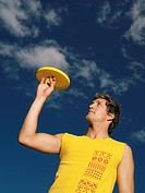 Young man balancing frisbee on his finger