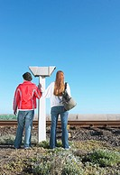 Teenagers standing next to railway tracks