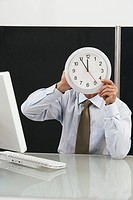 Man holding a wall clock in front of his face