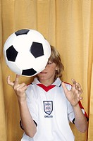Boy balancing a soccer ball on one finger