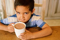 Skeptical little boy with mug of hot chocolate