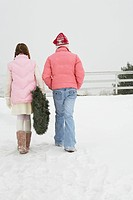 Two girls carrying a wreath in the snow