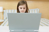 Young girl alone with a laptop computer