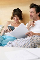 Couple working on their finances in bed