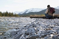 Man kneeling next to a river