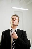Businessman loosening necktie