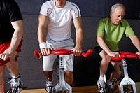 Three Men Riding Exercise Bicycles