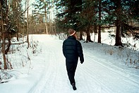 Woman Walking Down Snow Covered Path