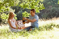 A young couple having a picnic, man opening a bottle of sparkling wine