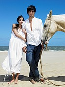 Young Couple and Horse on Beach