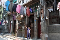 A senior hoisting laundry at the front of house at Xiguan, Guangzhou, China