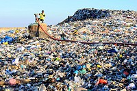 Landfill site. Worker at a landfill site. This site collects the methane gas released from household waste as it decomposes and burns it to produce el...