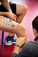 Fitness testing. Electrodes being placed on an athlete´s leg to monitor his muscles during a fitness test. Photographed at the INSEP Institut National...