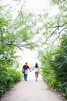 Couple holding hands, walking on path