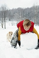 Boy with a giant snowball and dog