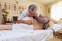 Physiotherapy. Physiotherapist carrying out gentle palpation and manipulation of the lower back to realign a patient´s facet joint between the fourth ...