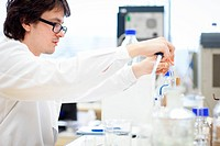 young male researche carrying out scientific experiments in a lab