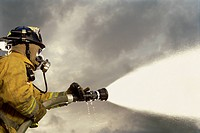 Low angle view of a firefighter in uniform spraying water against cloudy sky
