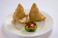 Indian fast food fried samosa potato filling maida wheat flour cover served with tomato ketchup in plate , India