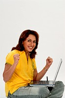 South Asian Indian woman working on laptop happy after reading good news on laptop ; Bombay Mumbai ; Maharashtra ; India MR682M