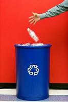 Man Putting Bottle into Recycling Bin