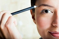 Woman using eyebrow pencil