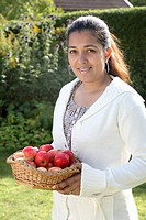 Young lady holding basket full of red apples MR468