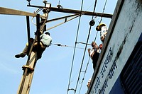 Railway workers repair high tension over head wires damaged after local derailed on Central line , Bombay Mumbai , Maharashtra , India