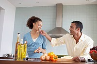 Young Man Feeding Young Woman Food in the Kitchen