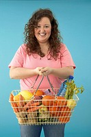 Overweight Woman Holding Shopping Basket Filled with Vegetables