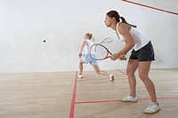Two Young Women Playing Squash