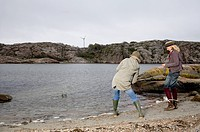 Young Women Skipping Rocks on Water
