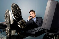 Young businessman wearing golf shoes at his desk